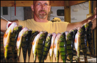 Owner of Balsam Beach Resort, Clint, holding a stringer of perch.